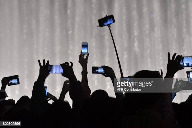 TOPSHOT People take photos and videoa of the water jest of the dancing fountains at the Dubai Mall during celebrations for Eid alFitr holiday that...