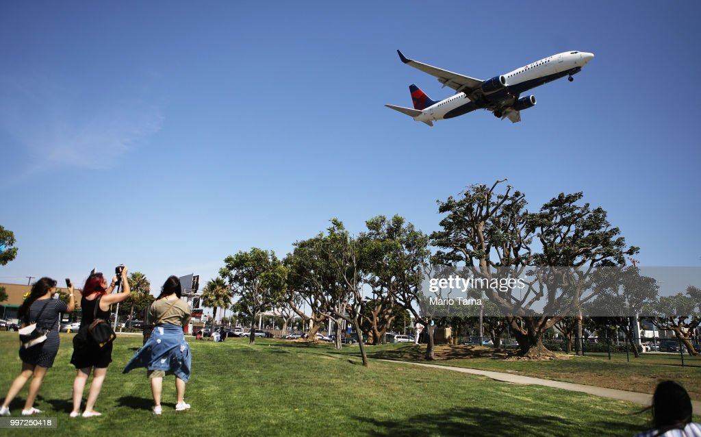 People take photos as a Delta Air Lines plane lands at Los Angeles International Airport on July 12, 2018 in Los Angeles, California. Delta announced today that it will increase fares by reducing the supply of seats in an effort to offset higher fuel prices.