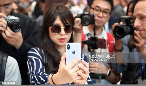 People take photos as a woman tests out a new iPhone X during a media event at Apple's new headquarters in Cupertino California on September 12 2017...