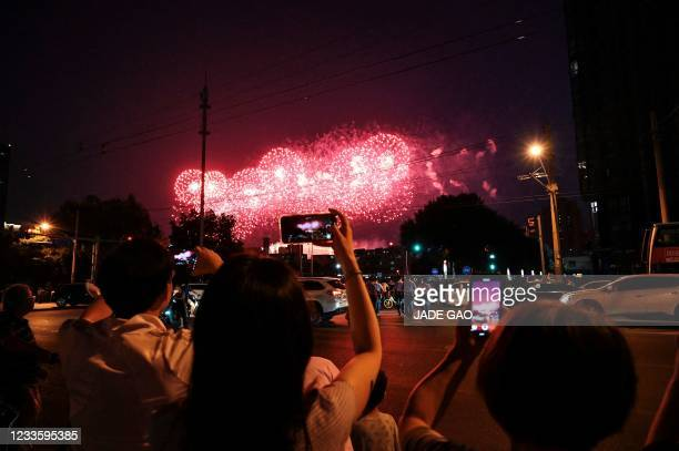 People take photos as fireworks explode overhead during a rehearsal of a performance marking the 100th anniversary of the founding of the Communist...