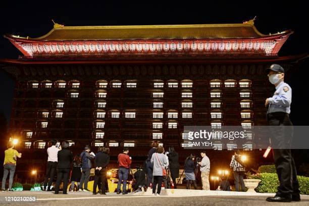 """People take photos as the rooms at the Grand Hotel are illuminated to form the word """"zero"""" after Taiwan reported no new COVID-19 coronavirus cases..."""