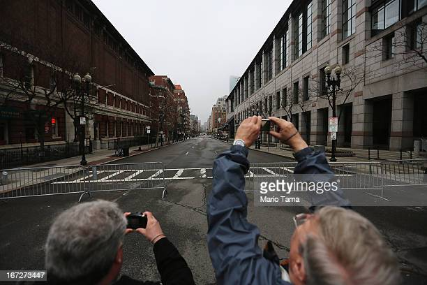 People take photos at a barricade blocking a still closed section of Boylston Street near the site of the Boston Marathon bombings on April 23 2013...