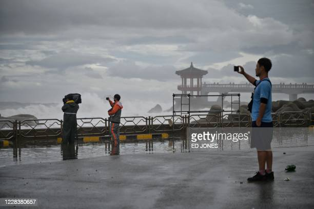 People take photos before a sea wall of waves brought by Typhoon Haishen in the eastern port city of Sokcho on September 7, 2020. - The powerful...