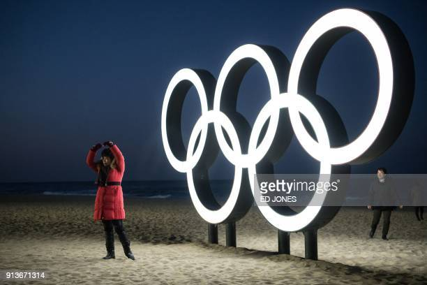 People take photos before the Olympic rings at Gyeongpo beach in Gangneung on February 3 2018 / AFP PHOTO / Ed JONES
