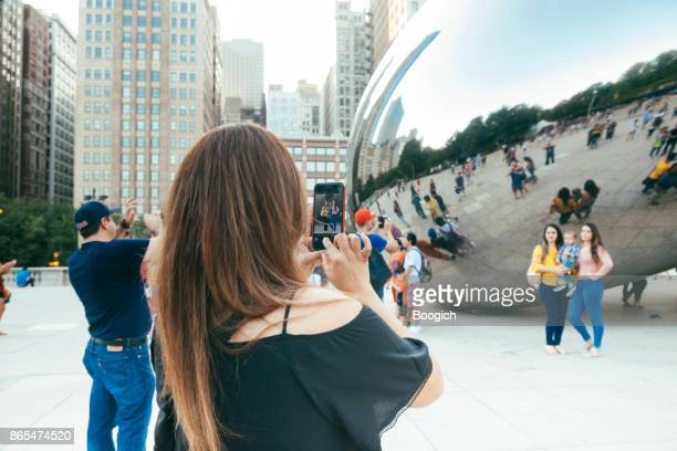 people take photos by chicago illinois cloudgate millennial park - cloud gate stock photos and pictures
