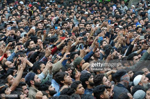 People take photos during a funeral procession of Jaish-e-Mohammed militant Naseer Pandith, at Karimabad on May 16, 2019 in Pulwama, India. Three...