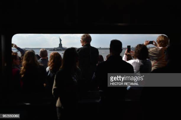 TOPSHOT People take photos from the Staten Island Ferry while looking at the Statue of Liberty in New York City on April 28 2018