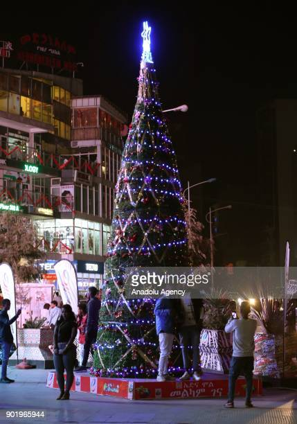 People take photos in front of a Christmas tree as they celebrate the Orthodox Christmas in Addis Ababa Ethiopia on January 6 2018