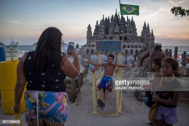 People take photos in front of the sand castle made by Marcio Mizael Matolias an artist known as 'The King' at Barra da Tijuca beach in Rio de...