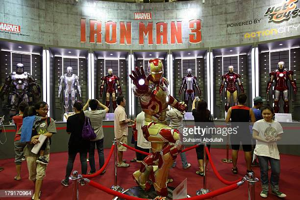 People take photos of a life size replica of Iron Man during the Singapore Toy Game Comic Convention at the Sands Expo Convention Centre at Marina...