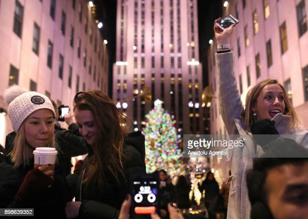 People take photos of a light show at Saks Fifth Avenue near the Christmas tree at Rockefeller Center on on December 26 2017 in New York City...