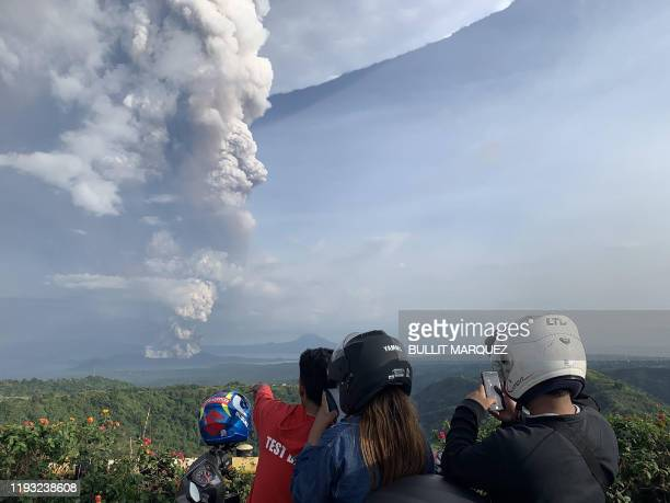 People take photos of a phreatic explosion from the Taal volcano as seen from the town of Tagaytay in Cavite province southwest of Manila on January...