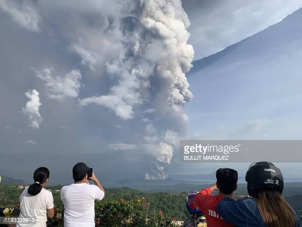 TOPSHOT People take photos of a phreatic explosion from the Taal volcano as seen from the town of Tagaytay in Cavite province southwest of Manila on...