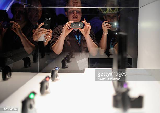 People take photos of a Playstation 4 and its controllers on display at the Sony Playstation E3 2013 booth at the Los Angeles Convention Center on...