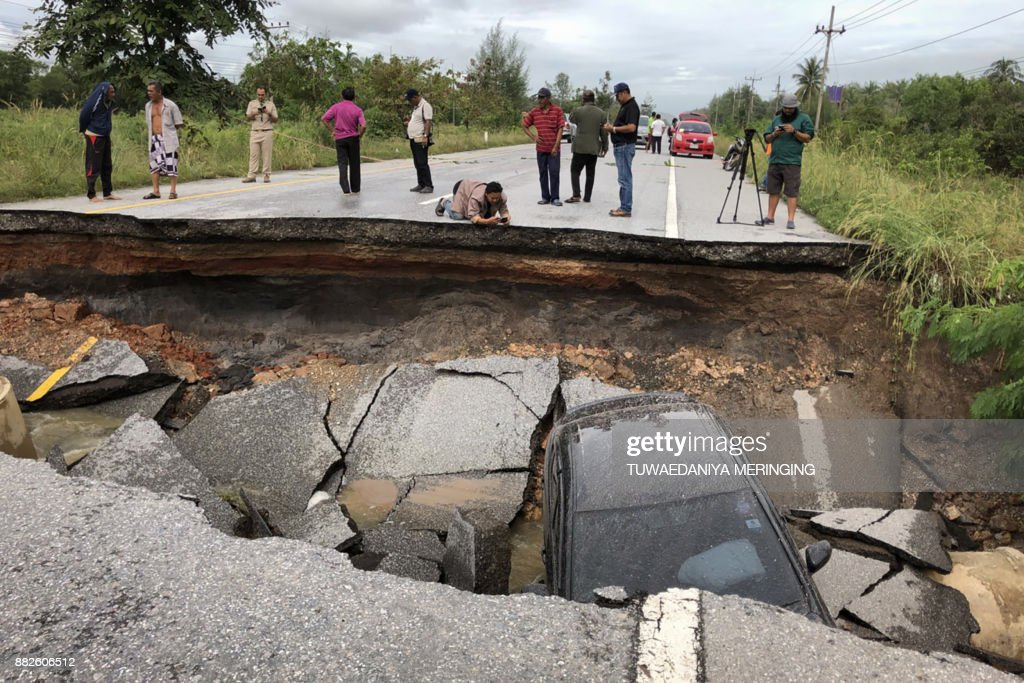TOPSHOT - People take photos of a road that collapsed due to heavy flooding in the southern Thai district of Songkhla on November 30, 2017. Heavy floods swept into southern Thailand this week killing five people, authorities said on November 30 as photos of waterlogged and damaged roads spread on social media. /