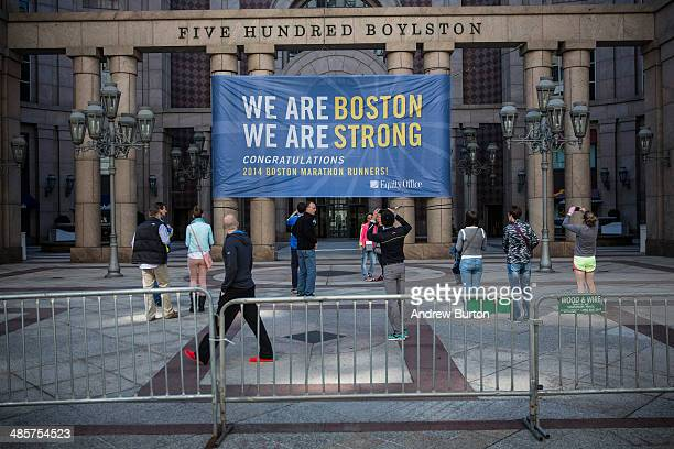 People take photos of a sign reading 'We are Boston We Are Strong' on Boylston Street where the Boston Marathon finishes on April 20 2014 in Boston...