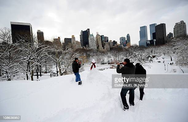 People take photos of a snowman standing in front of Manhattan's skyline after heavy snow falls in Central Park in New York January 27 2011 New York...