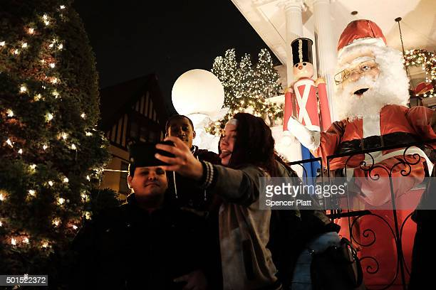 People take photos of Christmas lights and other ornaments outside of a home on December 15, 2015 in the Dyker Heights neighborhood of the Brooklyn...