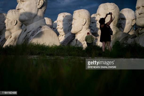 People take photos of decaying busts of former US Presidents during a night photography workshop organized by John Plashal August 25 in Williamsburg...