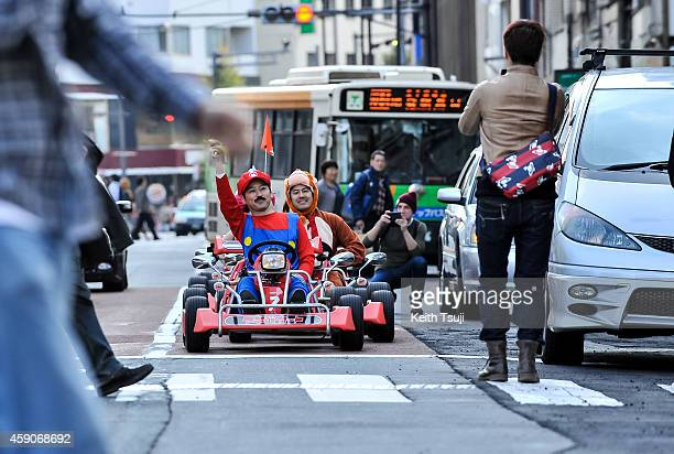 People take photos of participants as they drive around Tokyo in Mario Kart characters for the Real Mario Kart event in Tokyo on November 16 2014 in...
