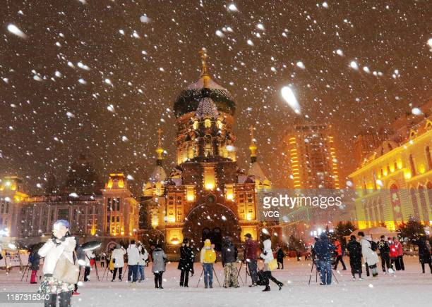 People take photos of Saint Sophia Cathedral in the first snow after the start of winter on November 12 2019 in Harbin Heilongjiang Province of China