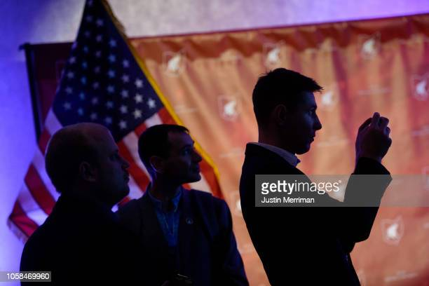 People take photos of the Fox News television screens as they wait for results at the Ohio Republican Party's election night party at the Sheraton...