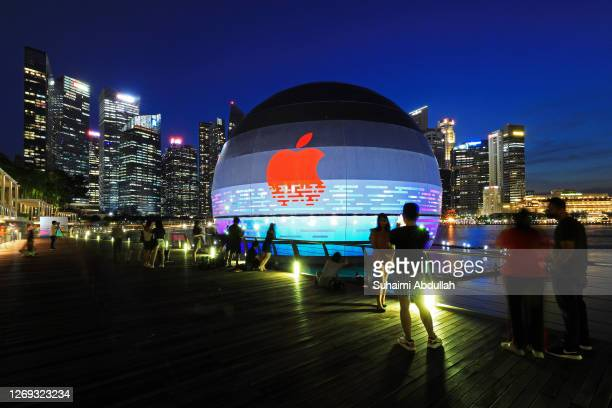 People take photos of the new Apple flagship store against the city skyline at Marina Bay Sands waterfront on August 28, 2020 in Singapore. The store...