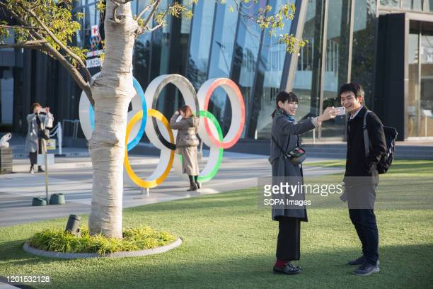 People take photos of the Olympic Rings near the Japan Olympic Museum and the New National Stadium in Kasumigaoka, Shinjuku, Tokyo, Japan. The...