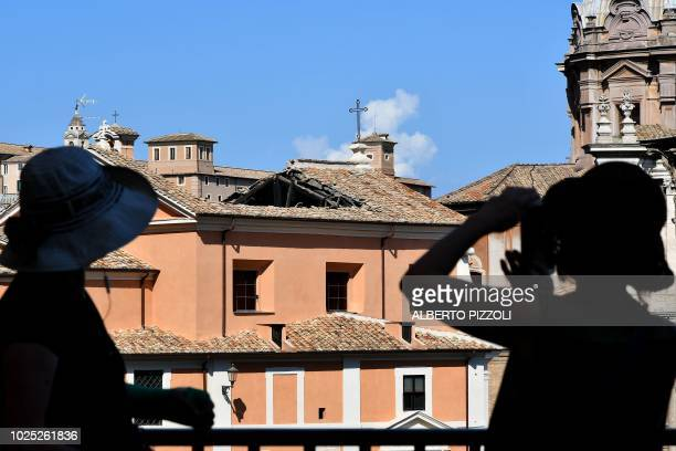 People take photos of the San Giuseppe dei Falegnami Church after its roof collapsed at the Roman forum in Rome on August 30 2018