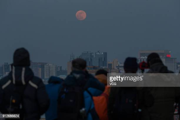 People take photos of the 'Super Blue Blood Moon' on January 31 2018 in Beijing China The moon turns red and blue during a total lunar eclipse on...