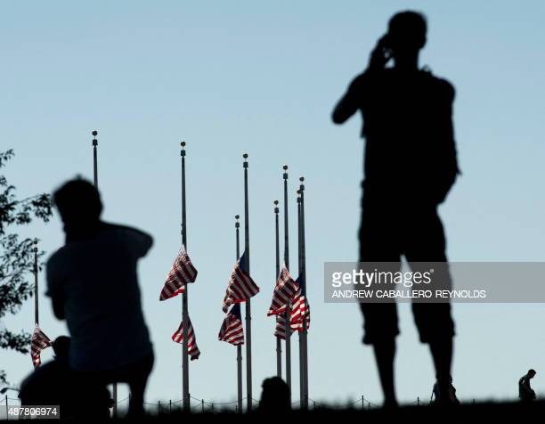 People take photos of US national flags flying at half mast at the Washington Monument in Washington DC on September 11 2015 As commemorations across...