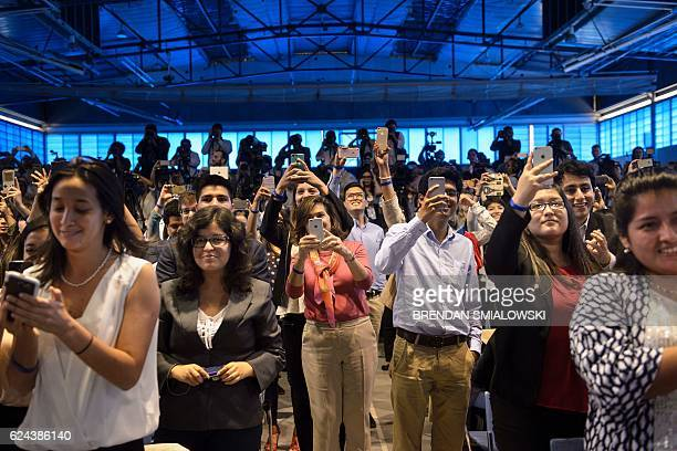 People take photos of US President Barack Obama during a Young Leaders of the Americas Initiative town hall meeting at the Pontifical Catholic...