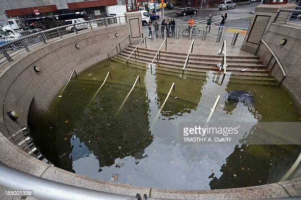 People take photos of water filling the entrance of The Plaza Shops in Battery Park in New York on October 30 2012 as New Yorkers cope with the...