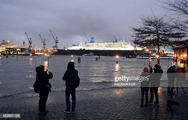 People take photos while looking at the water level of the Elbe river that flooded the area near the historic fish auction hall Fischmarkt on...