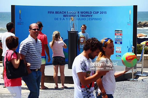 People take photos with the winners' trophy ahead of the FIFA Beach Soccer World Cup Portugal 2015 on July 5 2015 in Espinho Portugal