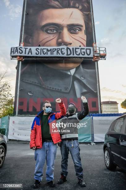 People take photos with their fists raised in front of street artist Jorit's mural of philosopher and politician Antonio Gramsci that pays tribute to...