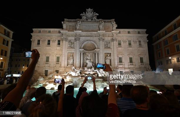 People take photos with their mobile phone of the Trevi Fountain illuminated with new lighting, on September 18, 2019 in central Rome.
