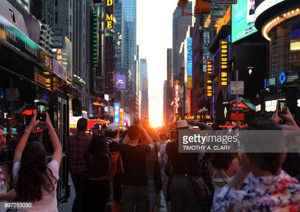 People take photos with their mobile phones as the sun sets as seen from 42nd street in Times Square in New York City on July 12 2018 during...