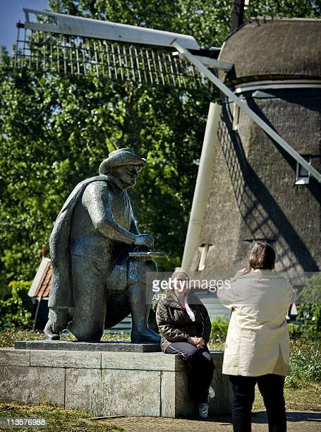 People take picture in front of a statue of Dutch painter Rembrandt by the Amstel in Amsterdam on May 3, 2011. The route Rembrandt walked between his...
