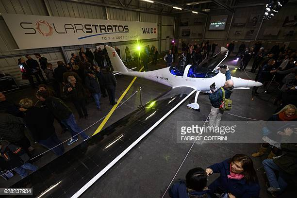 People take picture of the SolarStratos stratospheric powered aircraft after its rollout on December 7 2016 in Payerne Switzerland Swiss adventurer...