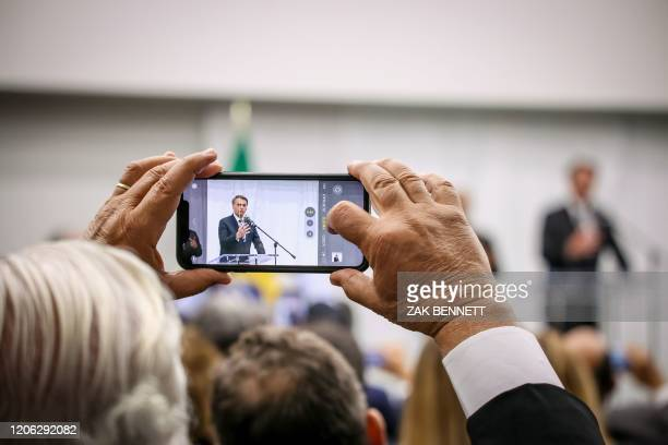 People take pictures and film Brazilian President Jair Bolsonaro as he speaks during an event at Miami's Brazilian community at Miami Dade College's...