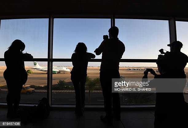 People take pictures as a Germania Airline flight carrying 141 German tourists arrives at the international airport of Egypt's Red Sea resort of...