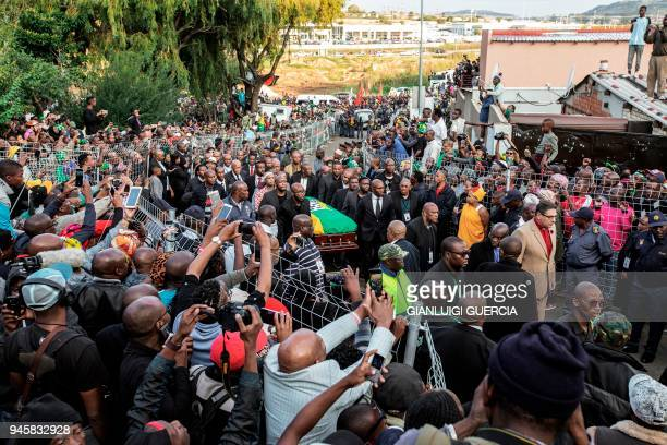 People take pictures as relatives carry the casket containing the body of the late Winnie Mandela at her house in Soweto in Johannesburg on April 13...