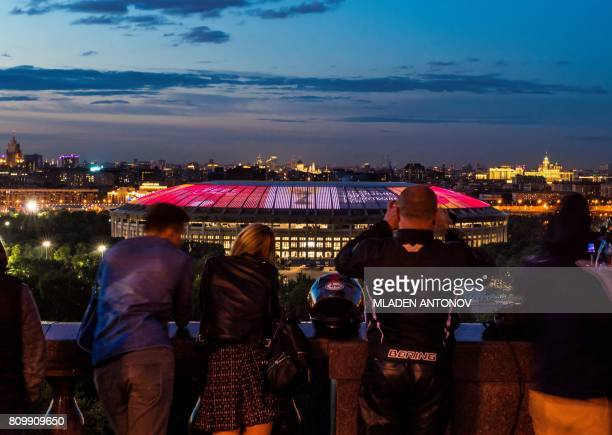 People take pictures as the FIFA World Cup Trophy is projected on the roof of the Luzhniki Olympic stadium marking the FIFA World Cup Trophy Tour...