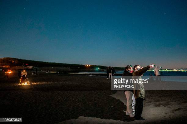 People take pictures as they gather at Southern Beach of Chigasaki to watch the sunrise on New Year's Day in Kanagawa Prefecture, southwest of Tokyo...