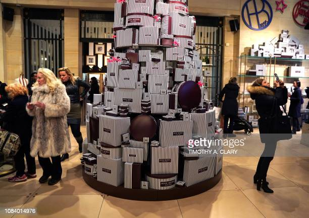 People take pictures at the luxury retailer Henri Bendel flagship store on 5th Avenue January 17 2019 on the last day of business for the iconic...