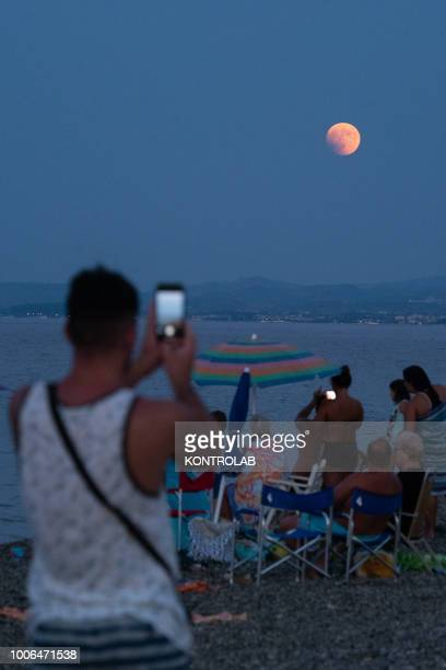People take pictures at the total eclipse of the moon which turns red on the Ionian sea The lunar eclipse is considered the longest eclipse of the...