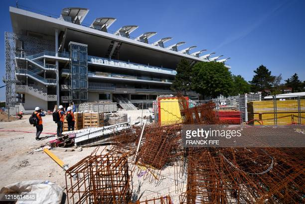 People take pictures during a visit on the construction site of the Philippe Chatrier central tennis court and of its newly built roof at the Roland...