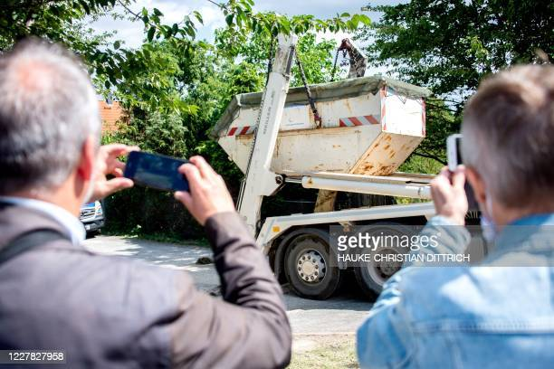 People take pictures from a skip being removed during a search by German police in a garden allotment in the northern German city of Hanover on July...