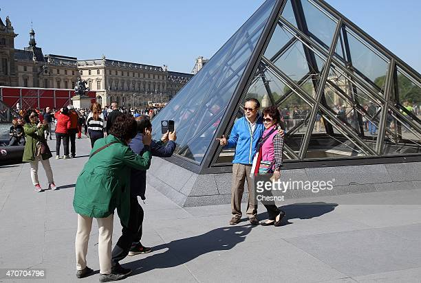 People take pictures in front of the Louvre Pyramid on March 22 2015 in Paris France France is still the leading tourist destination in the world...